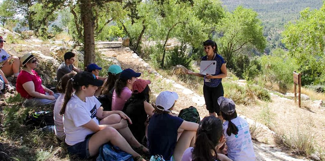 Young Judaea staff instructing teen on hillside